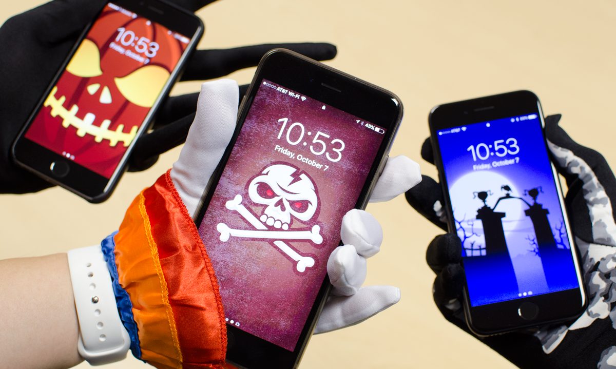 iPhones being held by costumed hands showing lock screens for Hack-O-Lantern, BoneHeadz & Ravenswood sticker packs